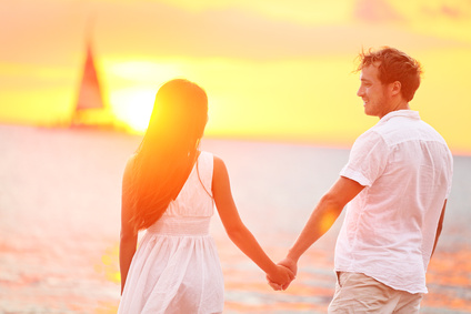 Couple in love happy at romantic beach sunset. Young interracial couple holding hands having romance and fun outside walking on beach during summer holidays vacation travel together. Enjoying sunshine